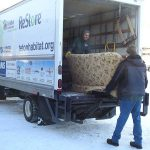 Unloading a donated couch from the back of a truck